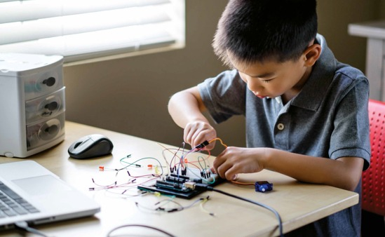 Young boy of color learns the fundamentals of programing with a simplified mother board